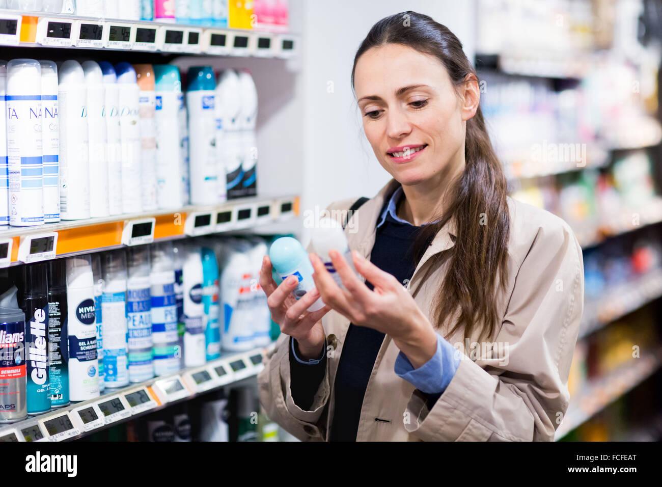 Mujer de compras en la sección de cuidado corporal en el supermercado. Imagen De Stock