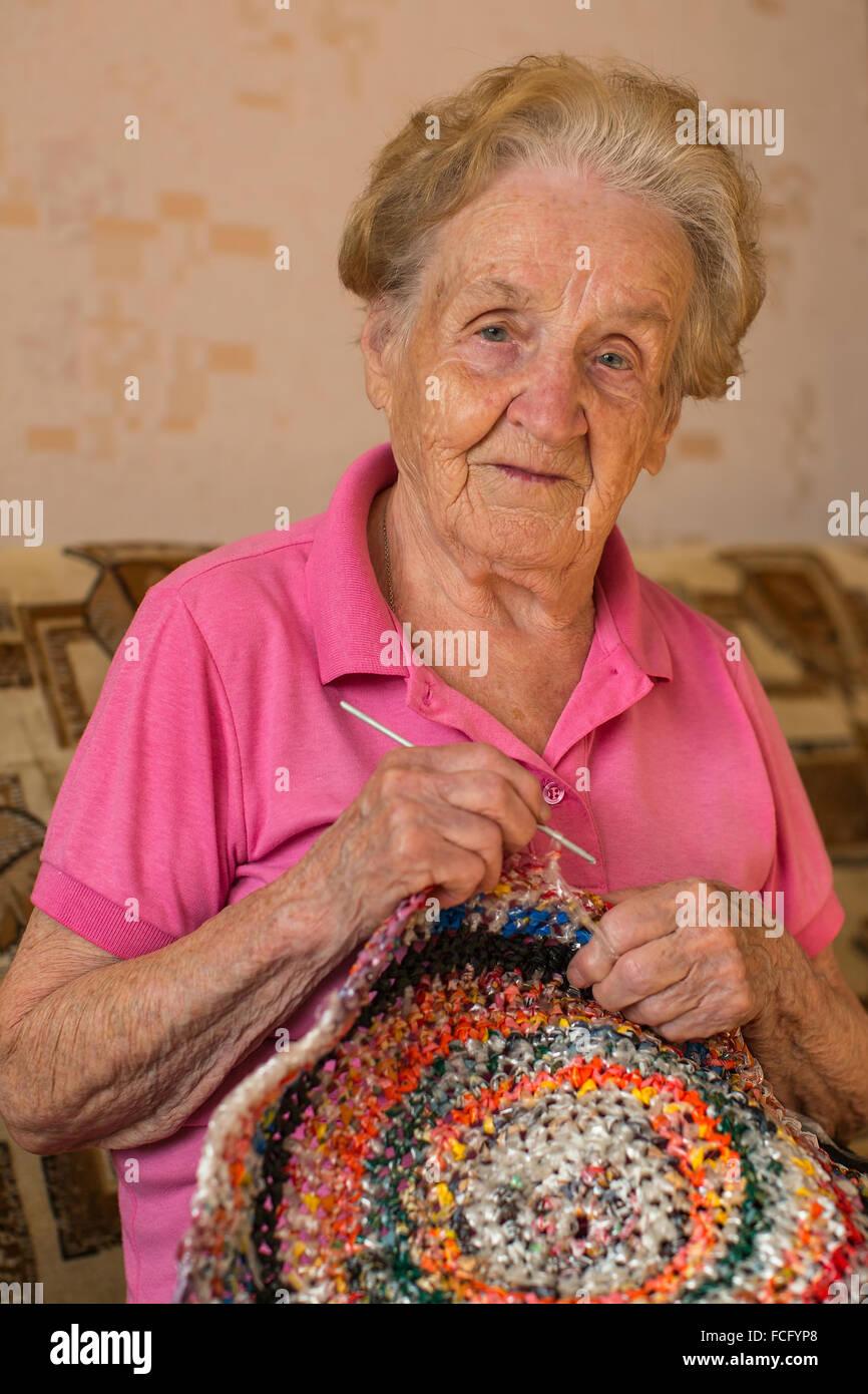 Una anciana mujer teje crocheting. Imagen De Stock