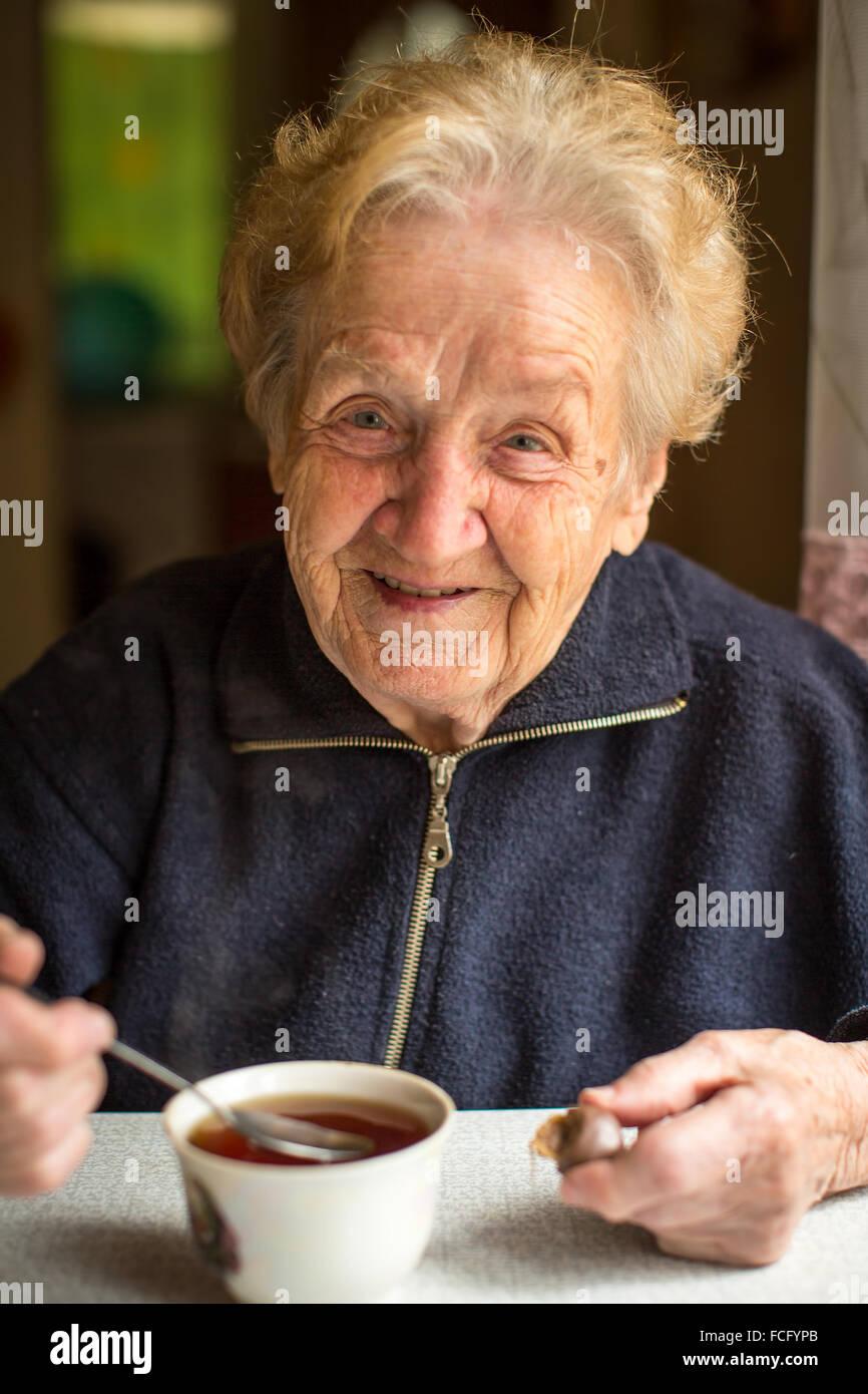 Anciana beber té en la cocina. Imagen De Stock
