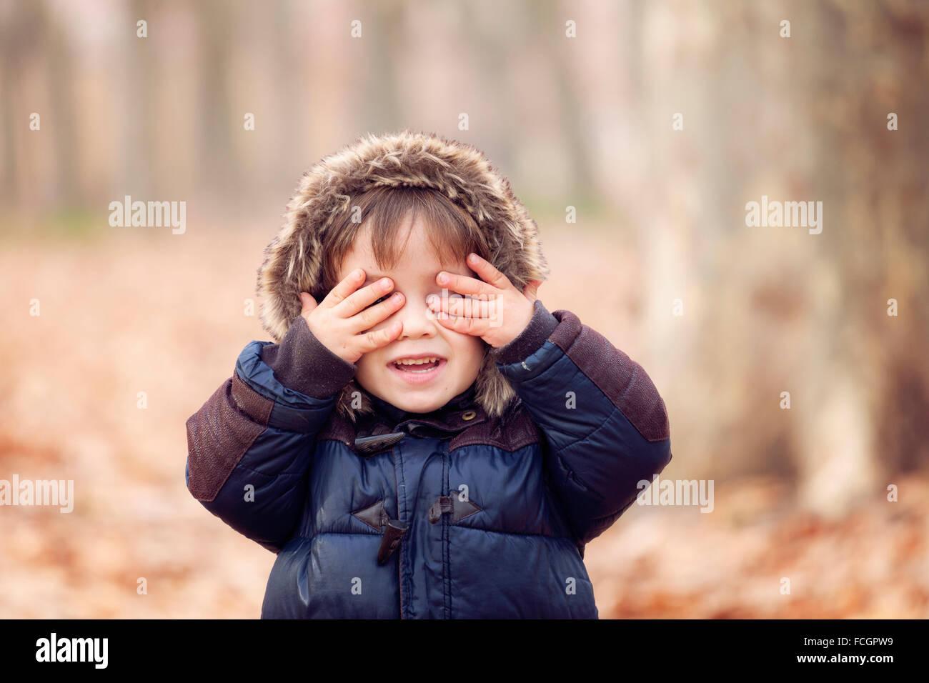 Chaqueta con capucha muchacho divertido ver ningún mal Imagen De Stock