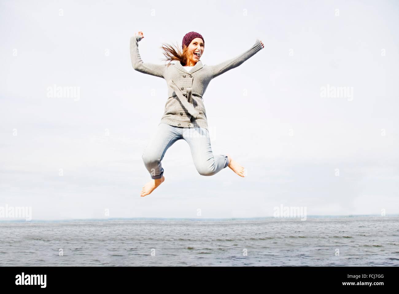 Mujer joven radiante de felicidad saltando por el mar Imagen De Stock