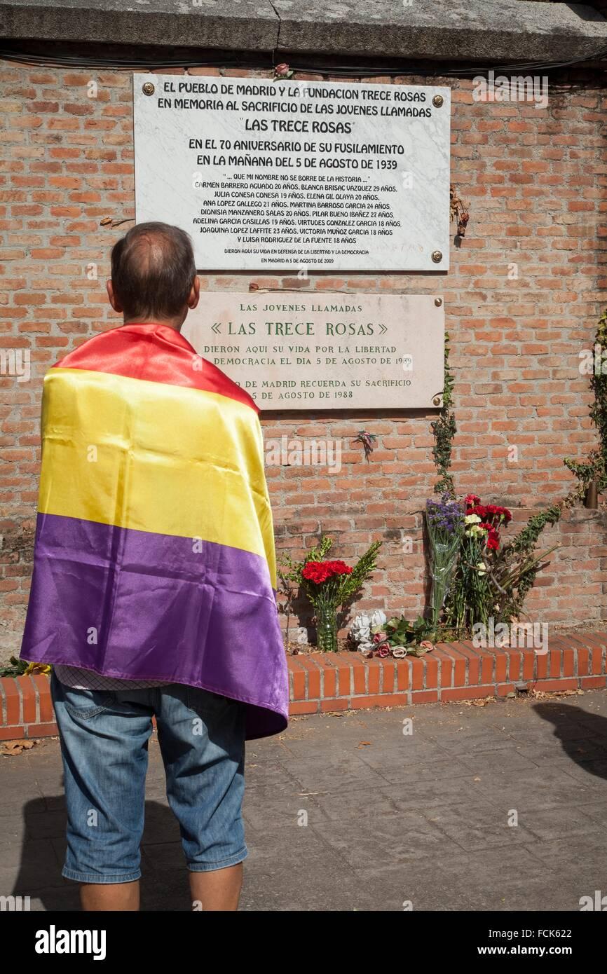 Hombre con bandera republicana delante de las lápidas homenaje a las trece rosas, homenaje a las 13 rosas en Imagen De Stock