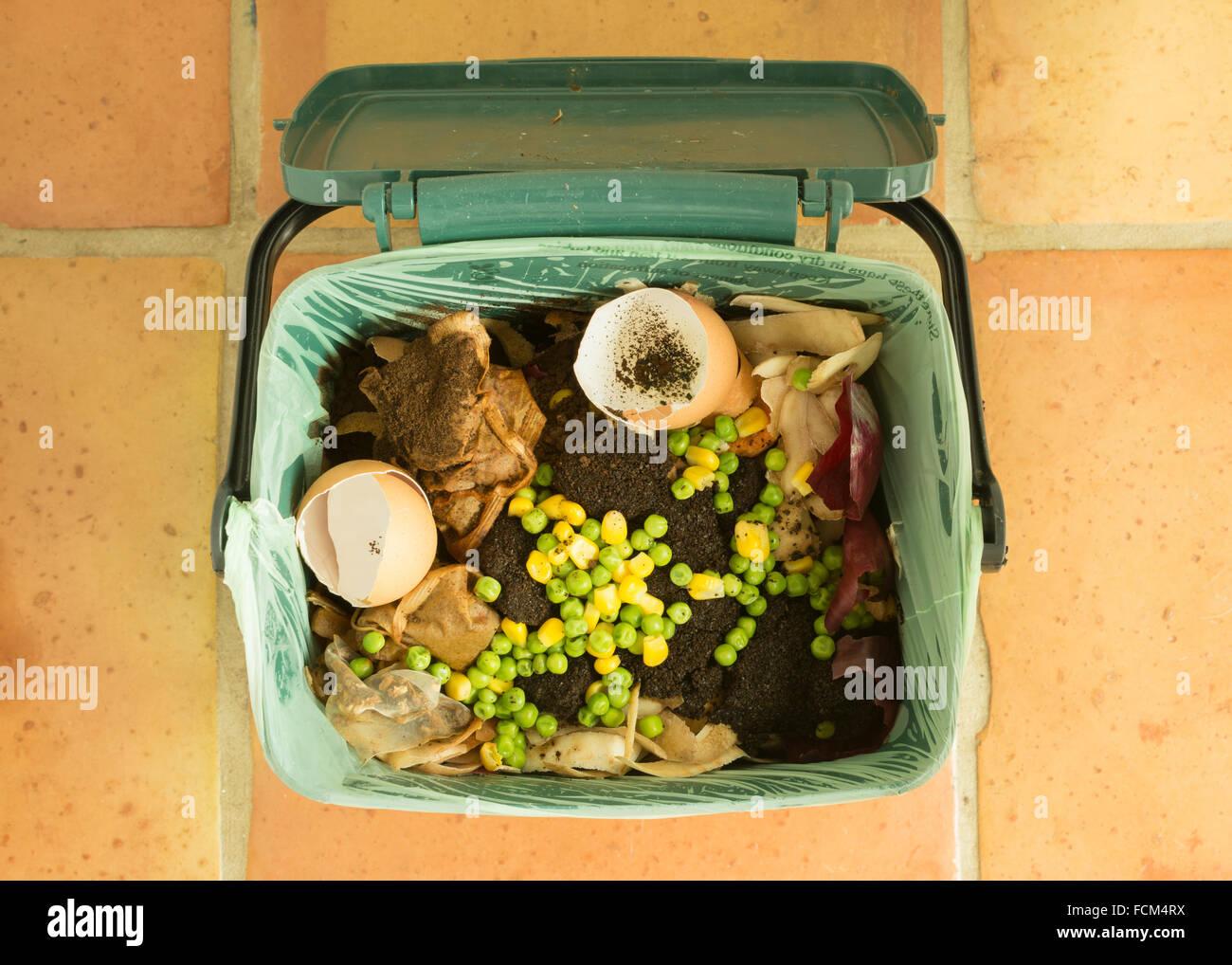 Los desperdicios de productos alimenticios - alimentos interiores caddy reciclaje llena de desechos de cocina para Imagen De Stock
