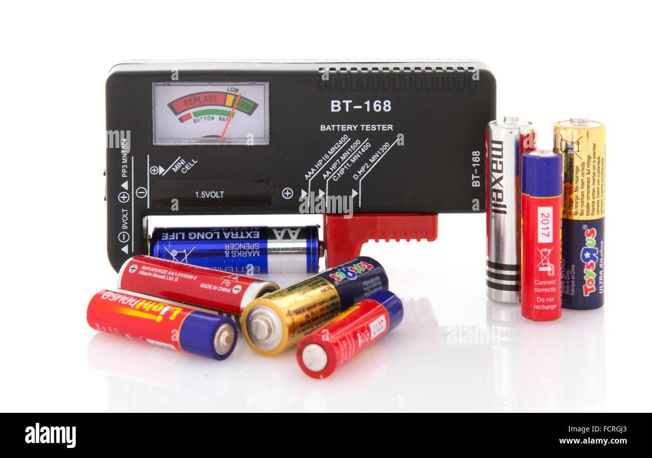 Probador de baterías con surtido de pilas secas para pruebas sobre un fondo blanco. Imagen De Stock
