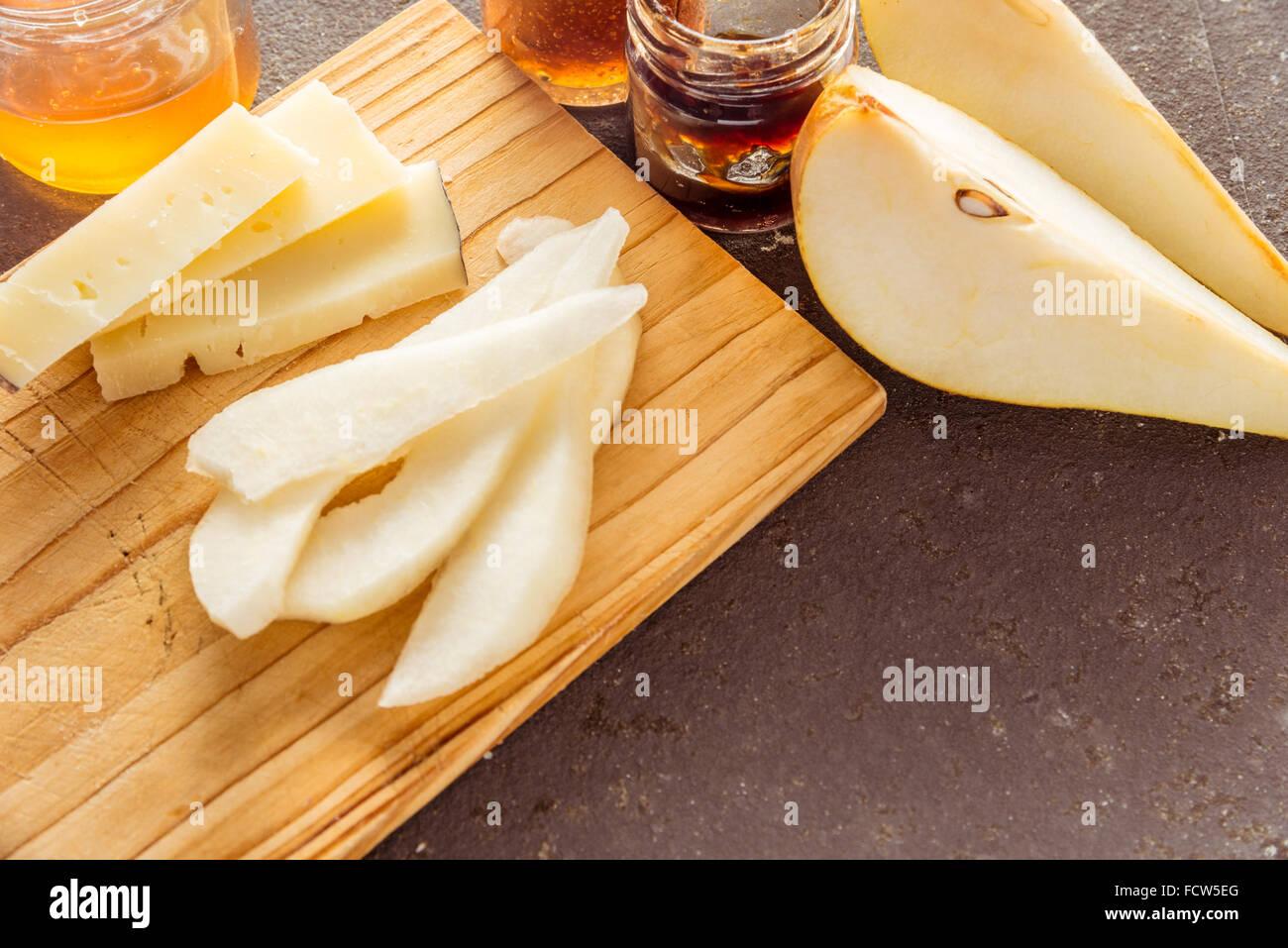 Una composición de italiano queso pecorino cortes con los atascos y las peras sobre una tabla de cortar de Imagen De Stock