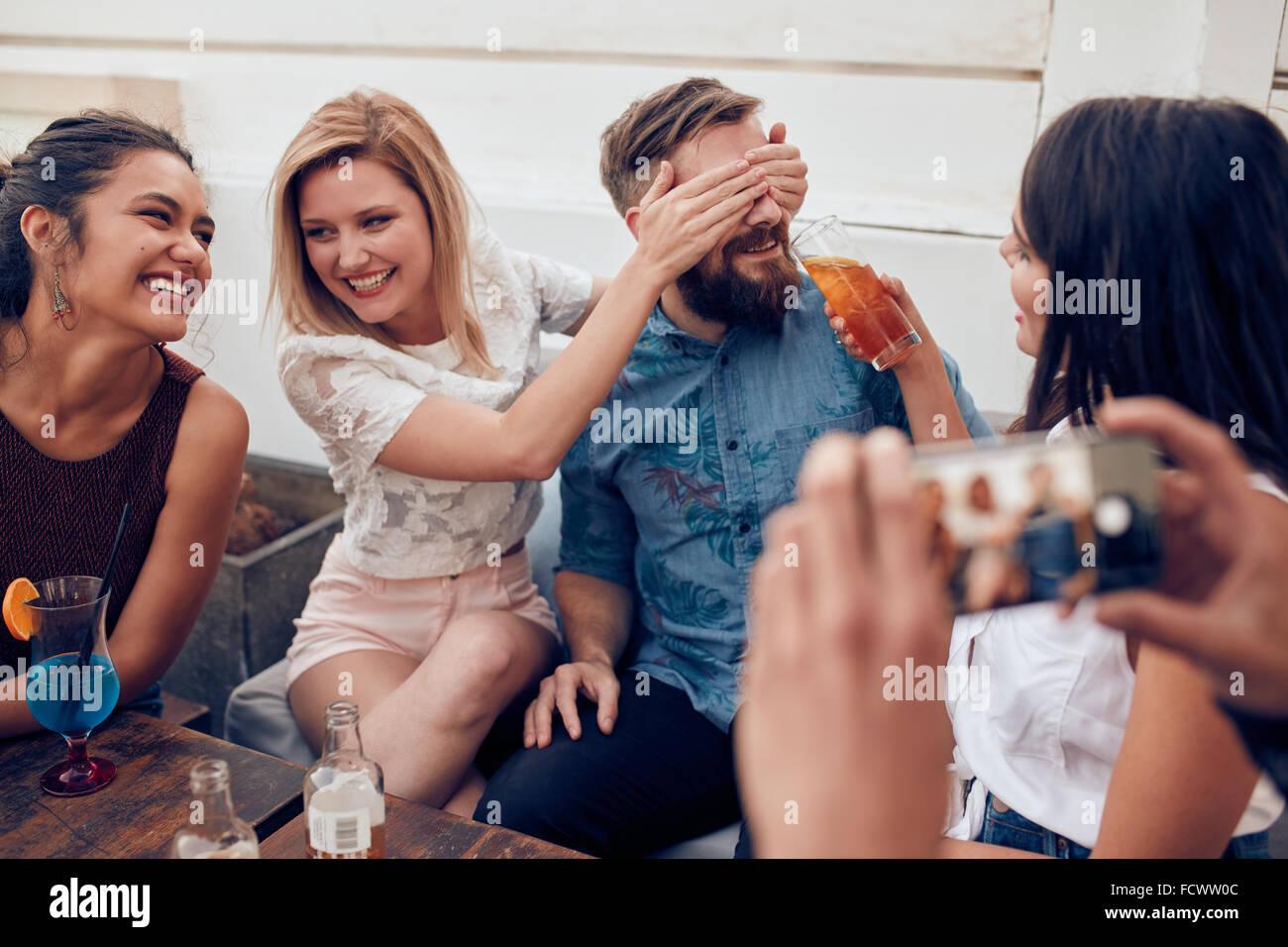 Los jóvenes sentados juntos disfrutando de partido. Mujer cerrando los ojos de un hombre con otro dando bebida. Imagen De Stock