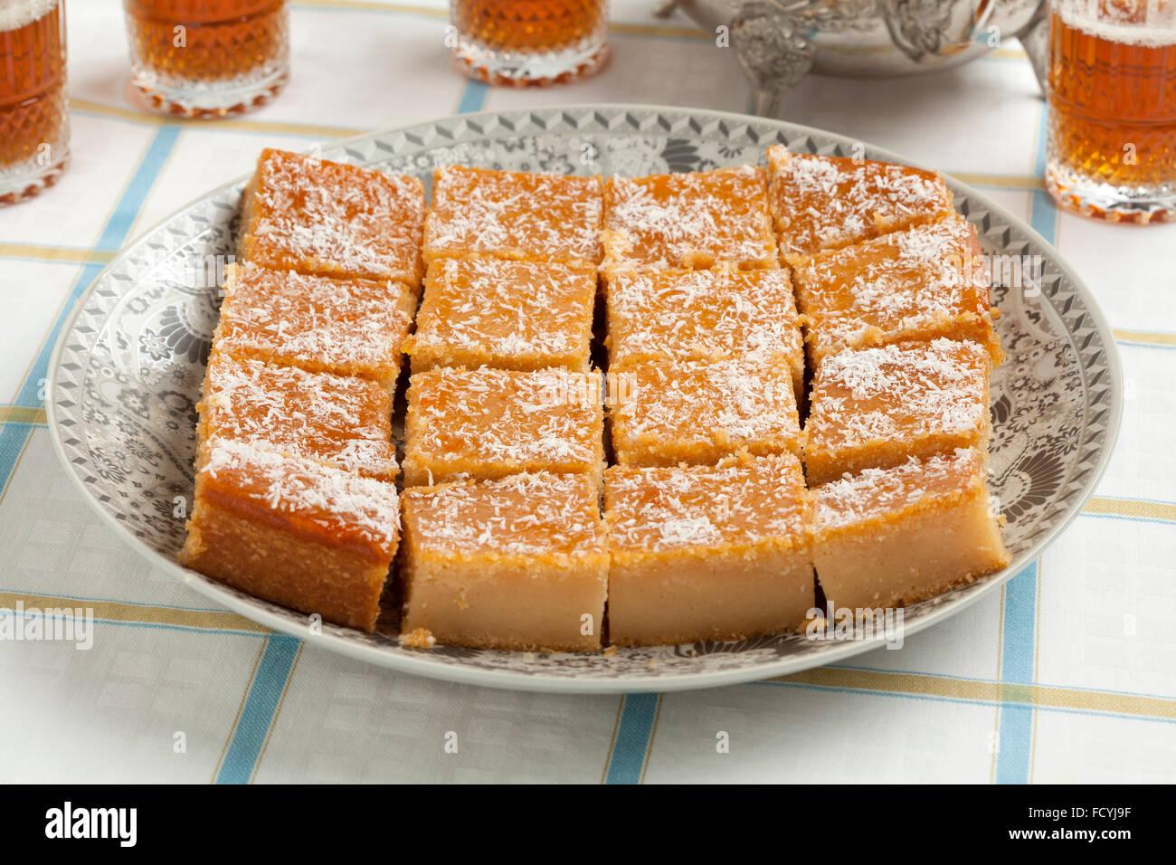 Pastel fresco de yogur marroquí cocido cortado en trozos y té para visitantes Imagen De Stock