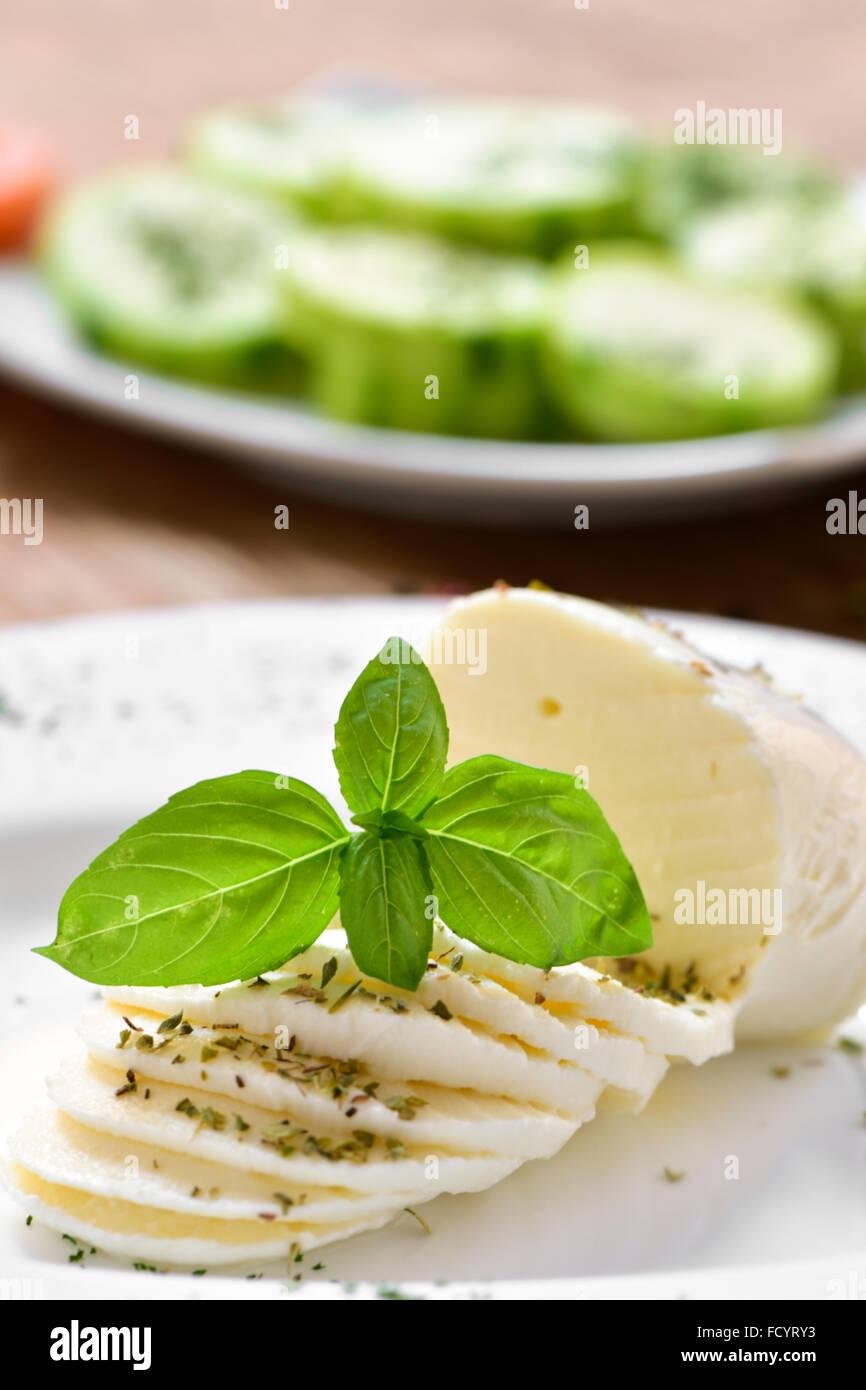 Primer plano de un plato con lonchas de queso fresco sobre una mesa, y una placa con la picada de calabacín Imagen De Stock