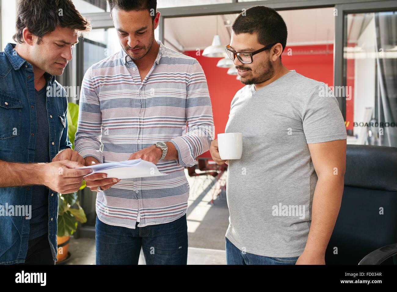 Grupo de jóvenes profesionales creativos tras una reunión en la oficina, pasando por algunos documentos Imagen De Stock