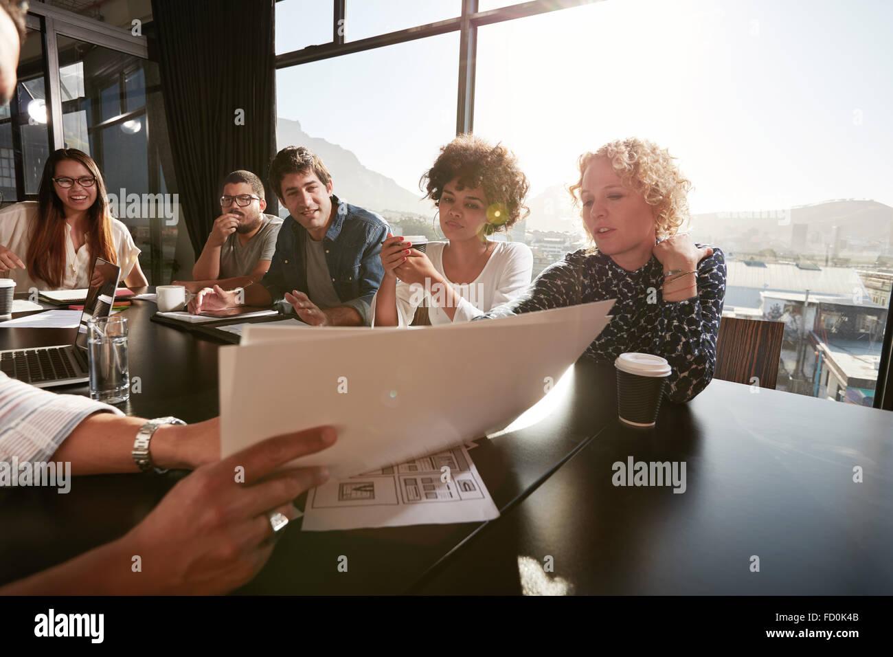 Acercamiento de las manos del joven explicando plan de negocios a sus colegas. Las personas creativas en la sala Imagen De Stock