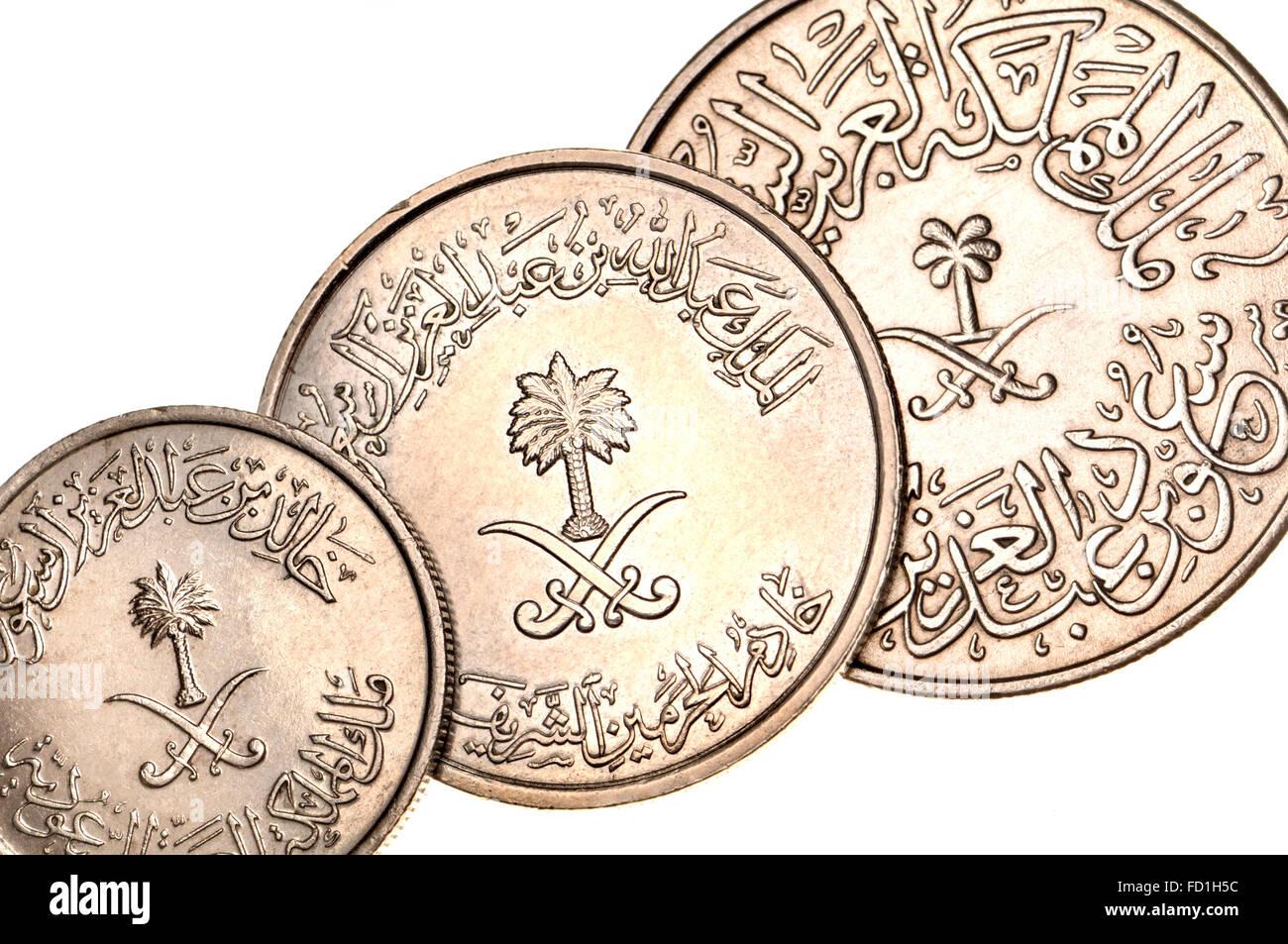 Las monedas de Arabia Saudita mostrando escritura árabe oriental y los numerales, palmera y espadas cruzadas Imagen De Stock