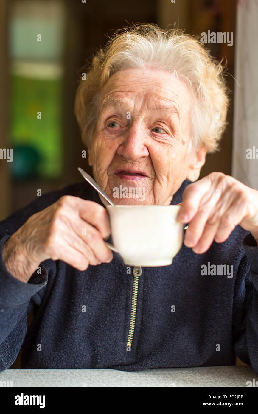 Retrato de una mujer anciana beber té. Imagen De Stock