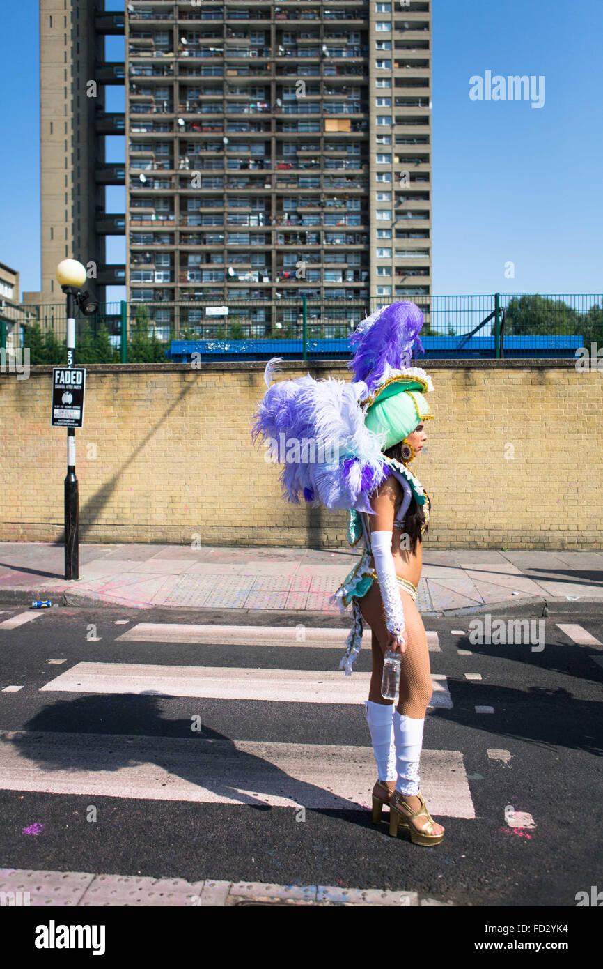 Bailarín de Paraiso escuela de samba esperando para unirse desfile con Trellick Tower en el fondo, el Carnaval Imagen De Stock