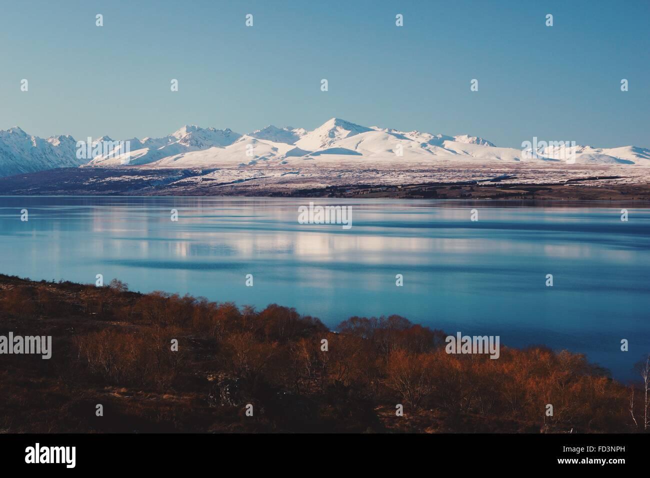 Agua Azul reflejo de montañas nevadas y bracken naranja en la Isla del Sur de Nueva Zelanda. Imagen De Stock