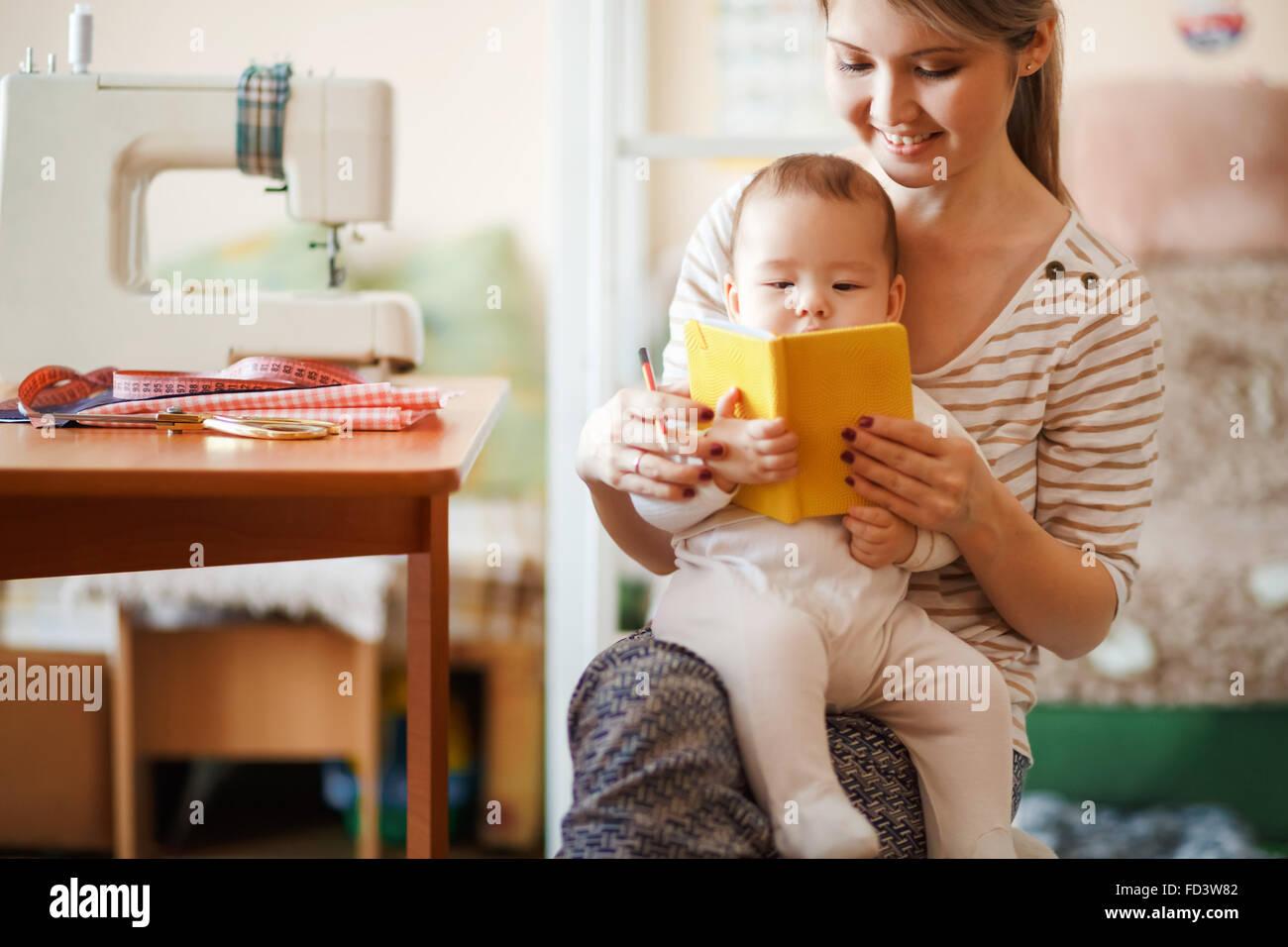 La madre y el bebé leyendo un libro juntos en casa. Imagen De Stock