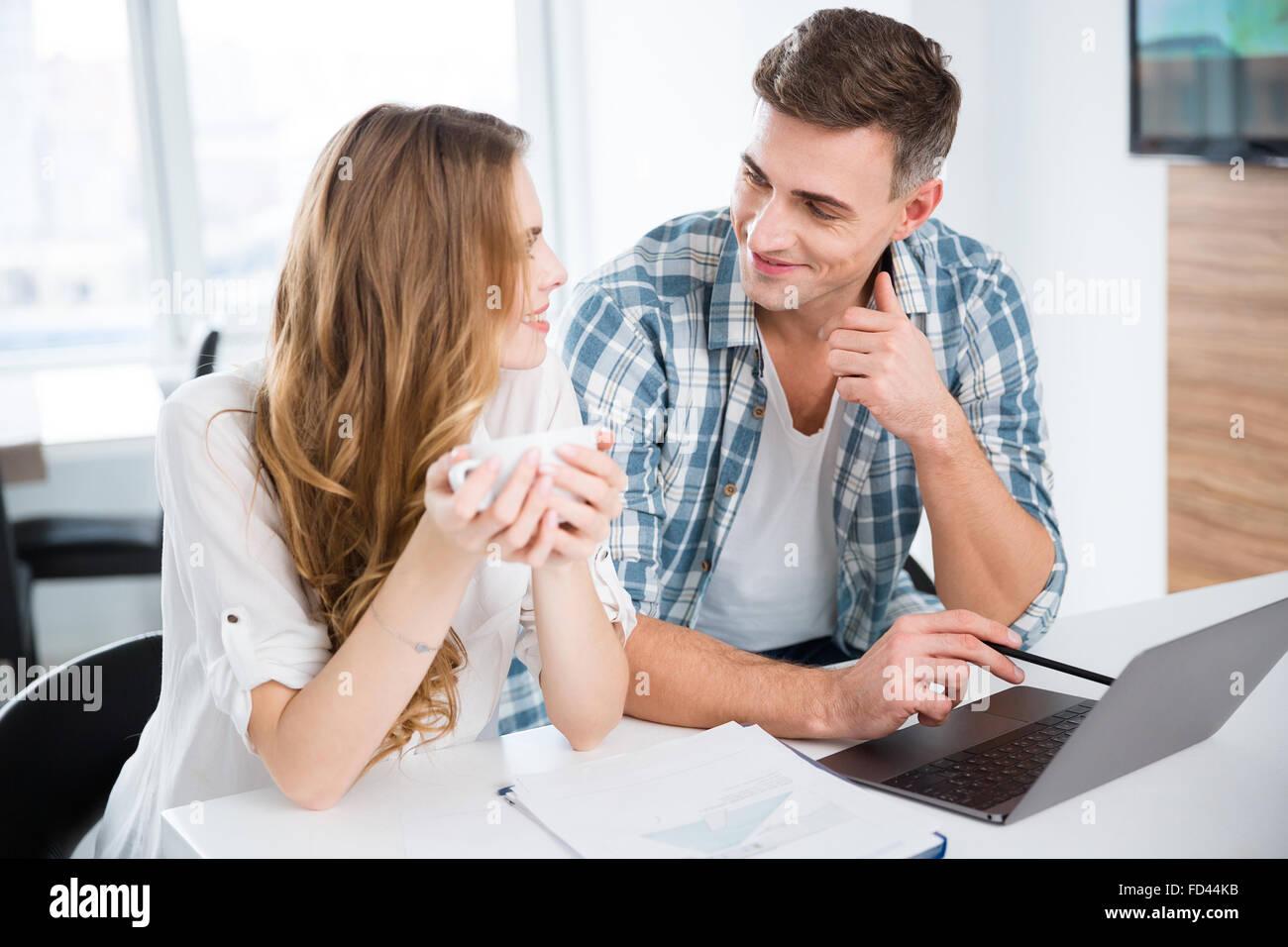 Compañeros sonrientes en ropa casual que trabajan con ordenador portátil y bebiendo café Imagen De Stock