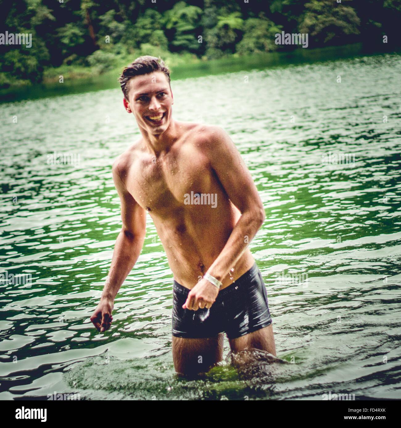 Feliz el hombre Descamisado joven húmedo en el lago Imagen De Stock