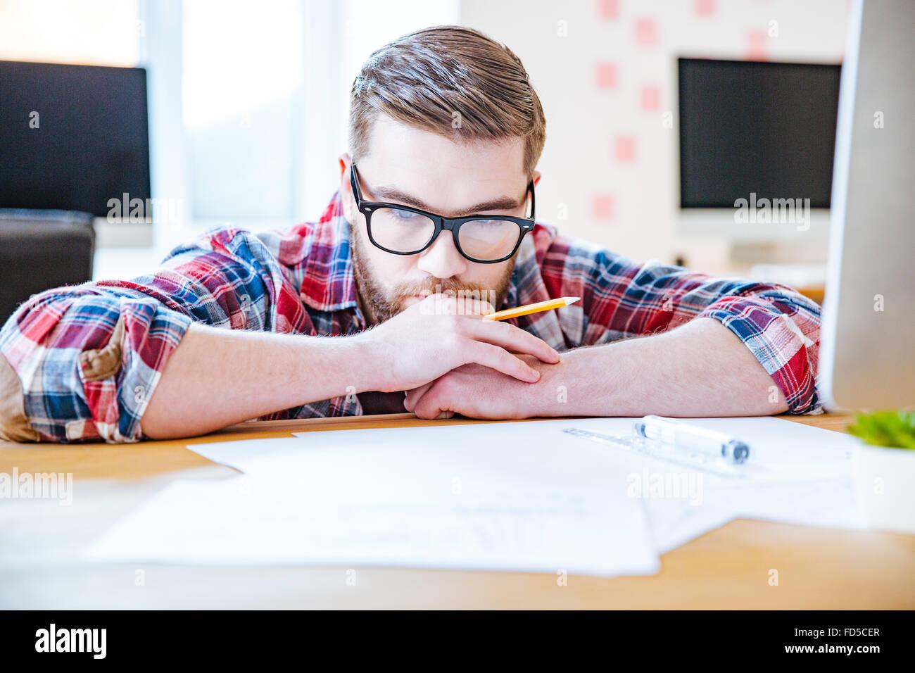 Joven barbudo reflexiva en vidrios trabaja con blueprits utilizando un lápiz y una regla en la oficina Imagen De Stock