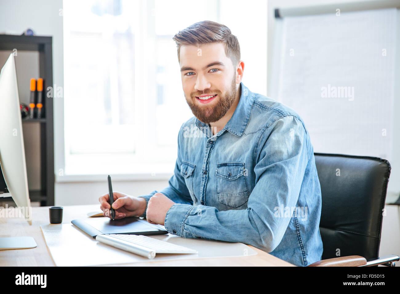 Retrato de feliz atractivo diseñador joven en jeans shirt trabaja con pen tablet con lápiz en Office Foto de stock