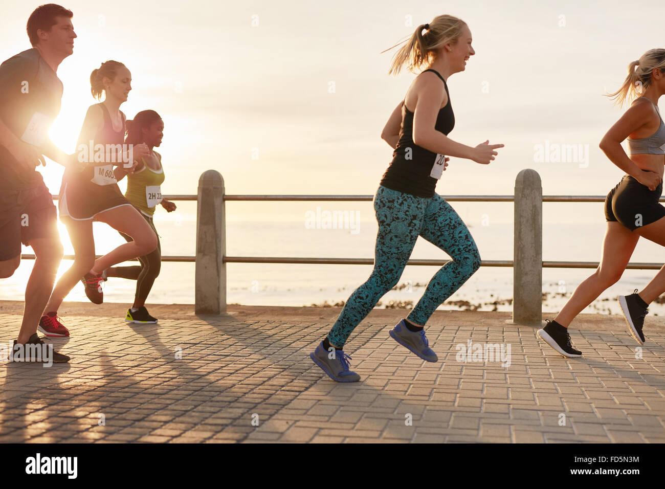 Retrato de jóvenes corriendo en el paseo marítimo. Hombres y mujeres corriendo maratón en carretera Imagen De Stock
