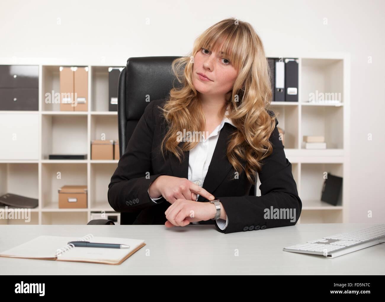 Directora sentada en su escritorio en la oficina, apuntando a su reloj haciendo un punto que alguien es tarde para Imagen De Stock