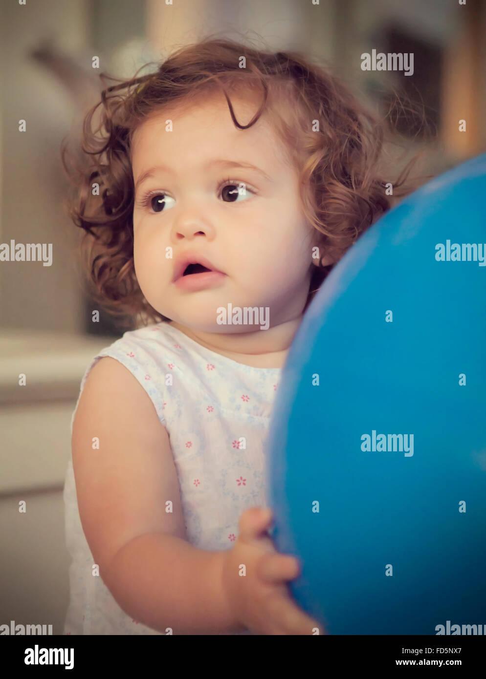 Niño Niña con cabello castaño rizado mirando hacia el lado sujetando una gran  bola azul. 1e3147dfce0