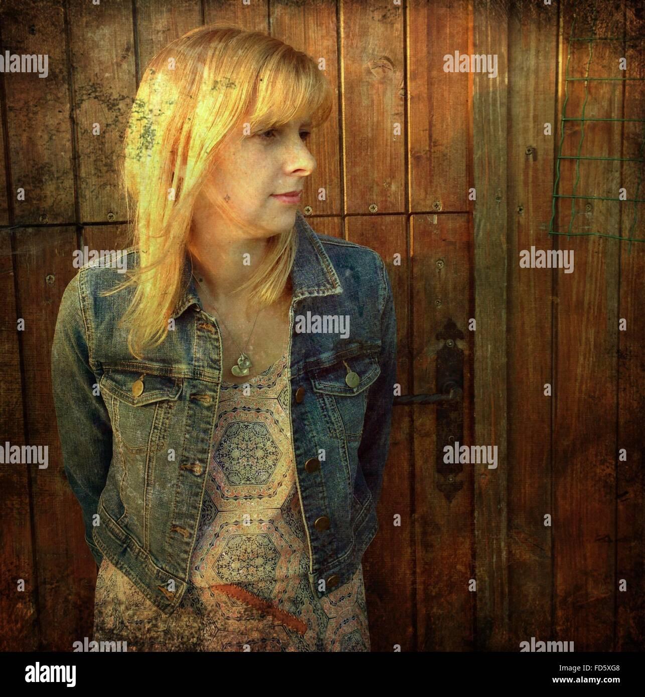 Mujer de pie fuera de la casa Foto de stock