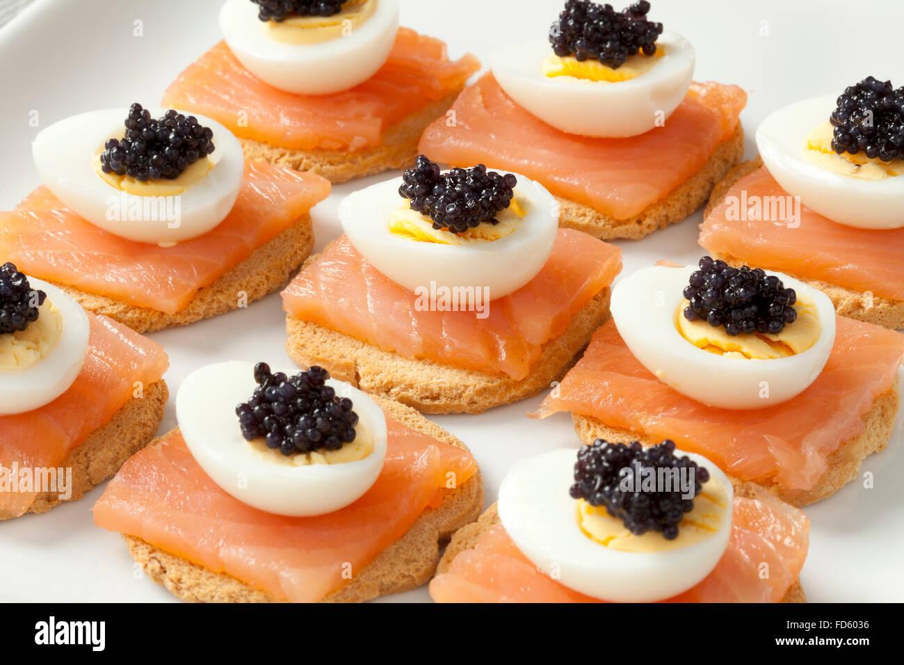 Snack con salmón, huevos de codorniz y lump roe sobre pan tostado Imagen De Stock