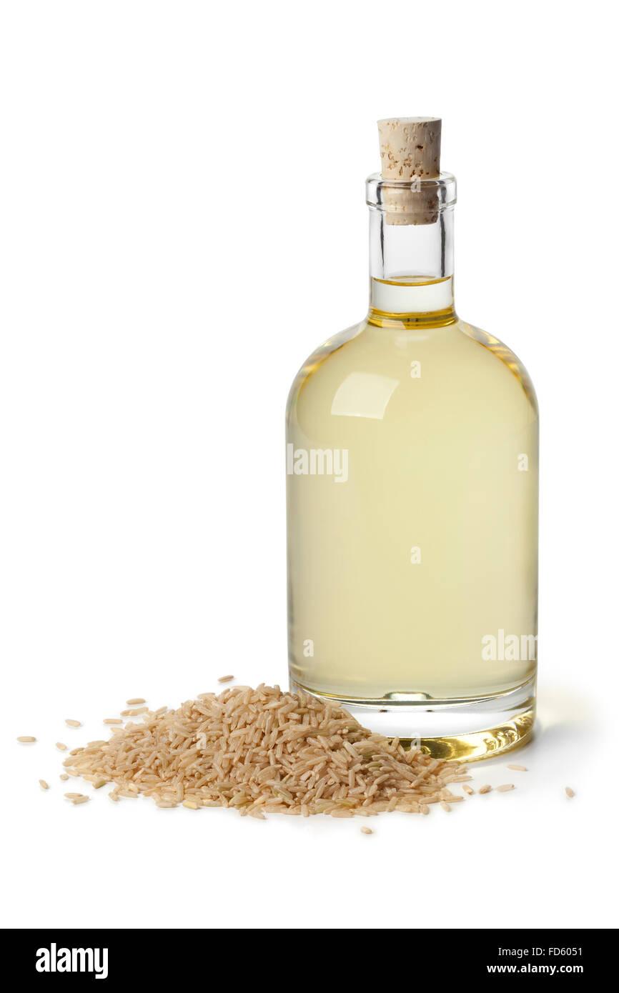 El aceite de arroz en una botella sobre fondo blanco. Imagen De Stock
