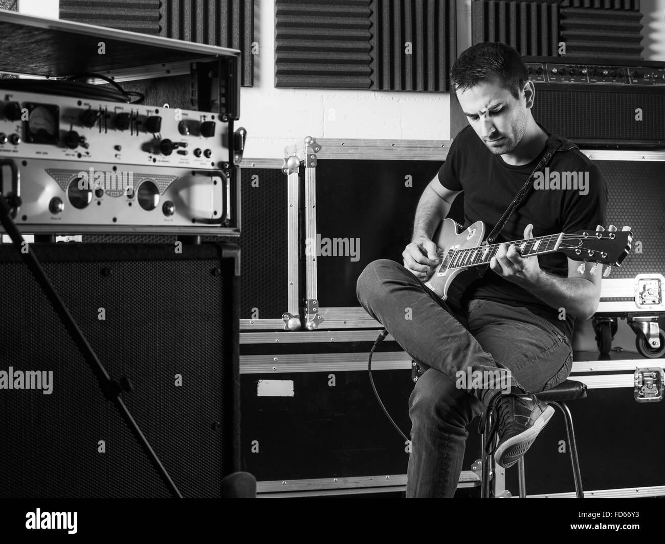Foto de un hombre sentado backstage practicando su guitarra. Imagen De Stock