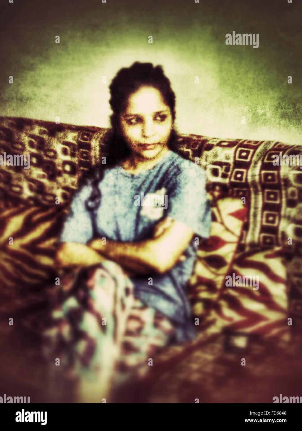 Mujer sentada en un sofá y pensando Imagen De Stock