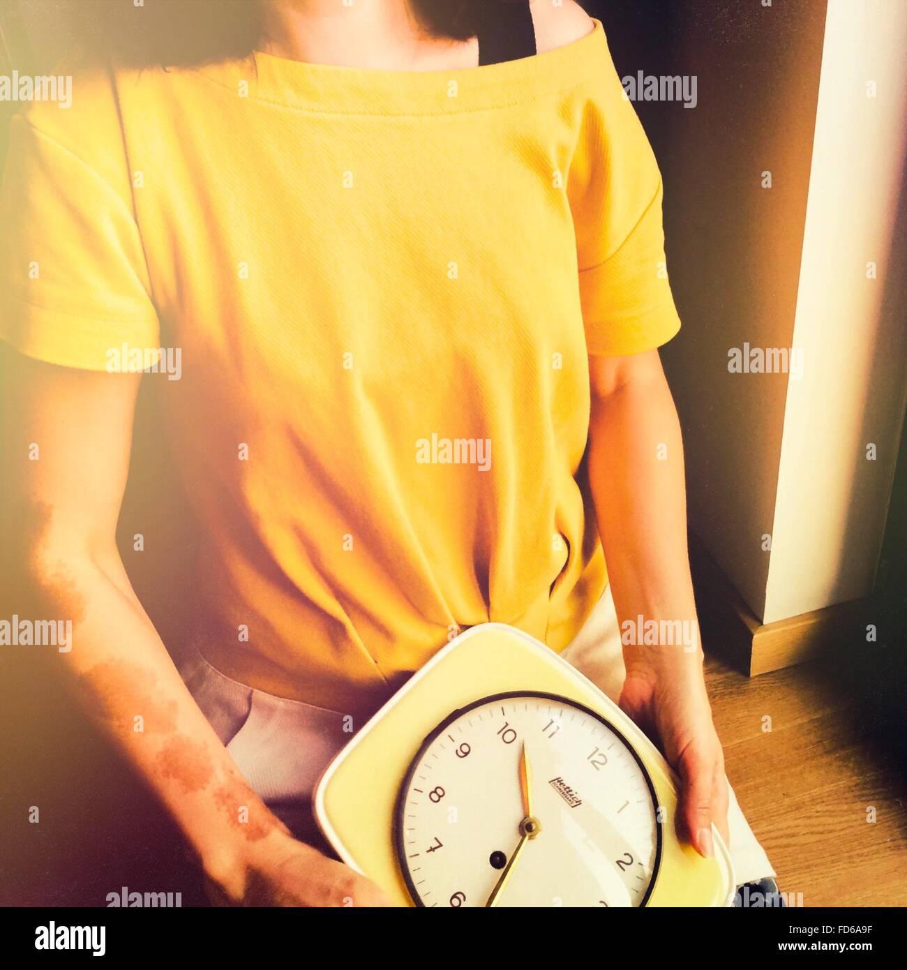 Mujer sosteniendo un reloj Imagen De Stock