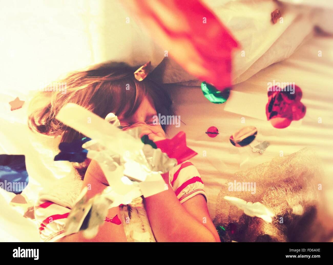Chica acostada en la cama arrojando confeti y riendo Imagen De Stock