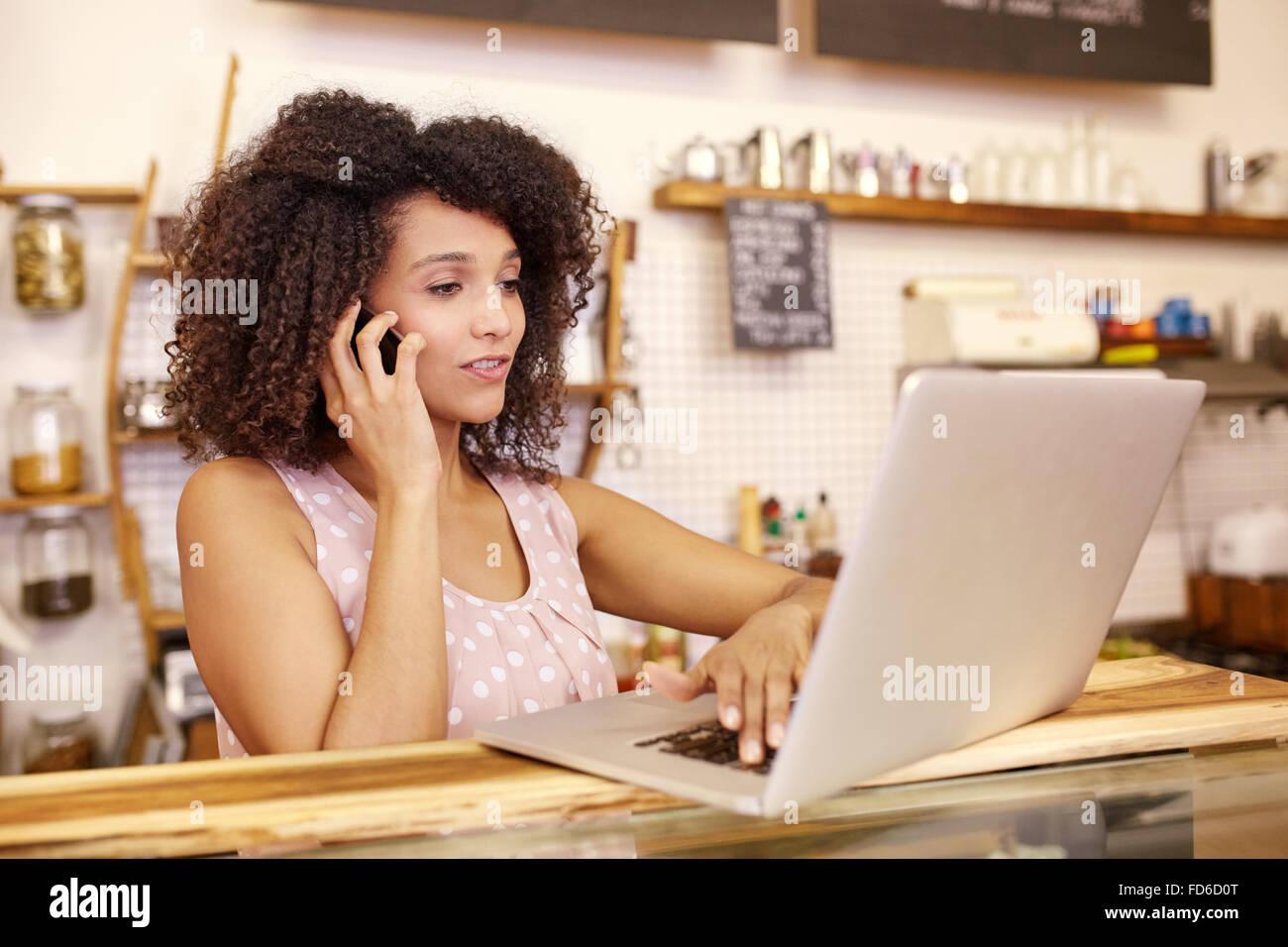 Propietario de negocio en el teléfono y escribir portátil Imagen De Stock