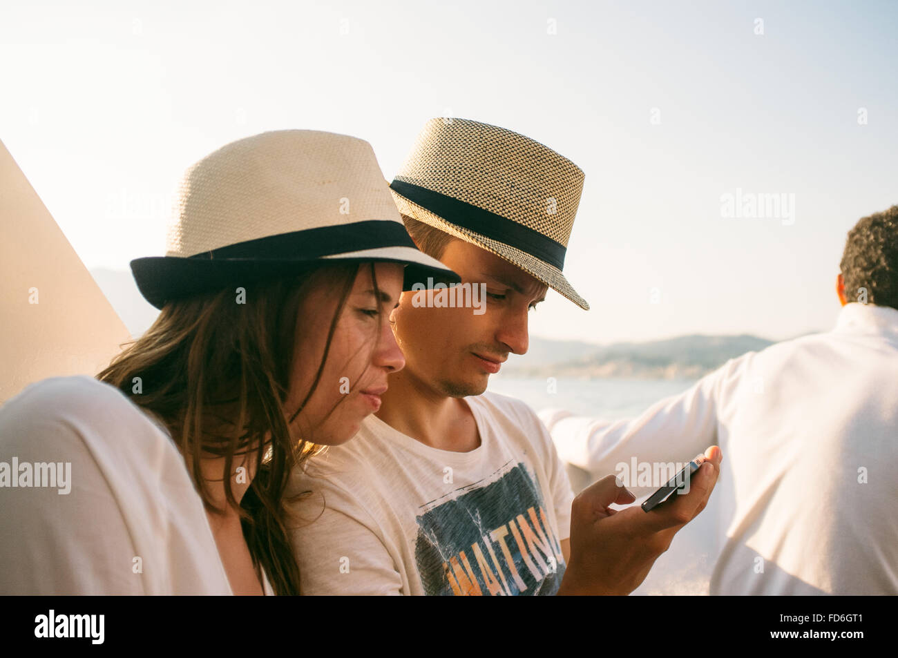 Pareja joven con sombrero utilizando Smart Phone en la playa Imagen De Stock