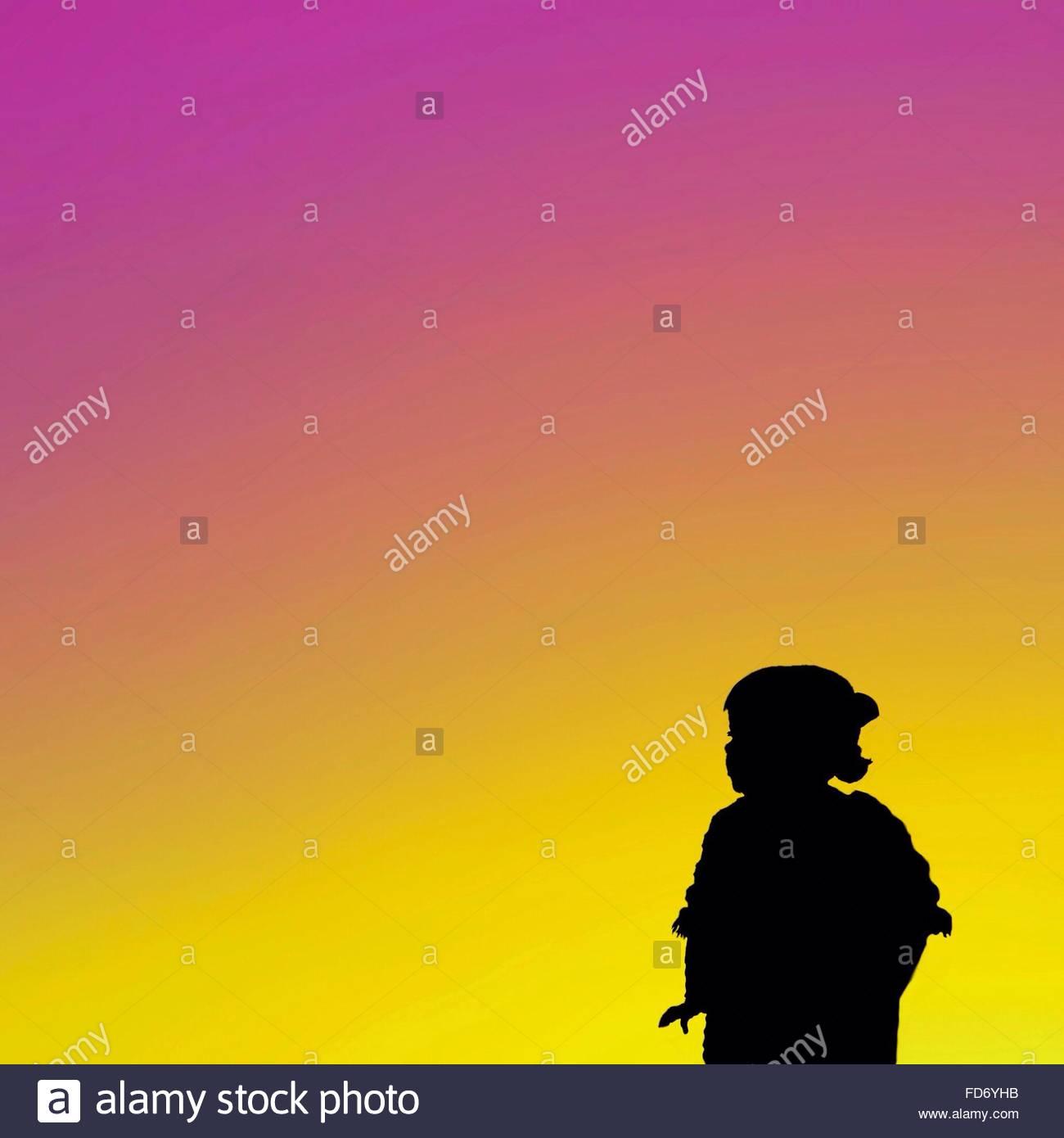 Silueta niña contra el espectacular cielo Imagen De Stock