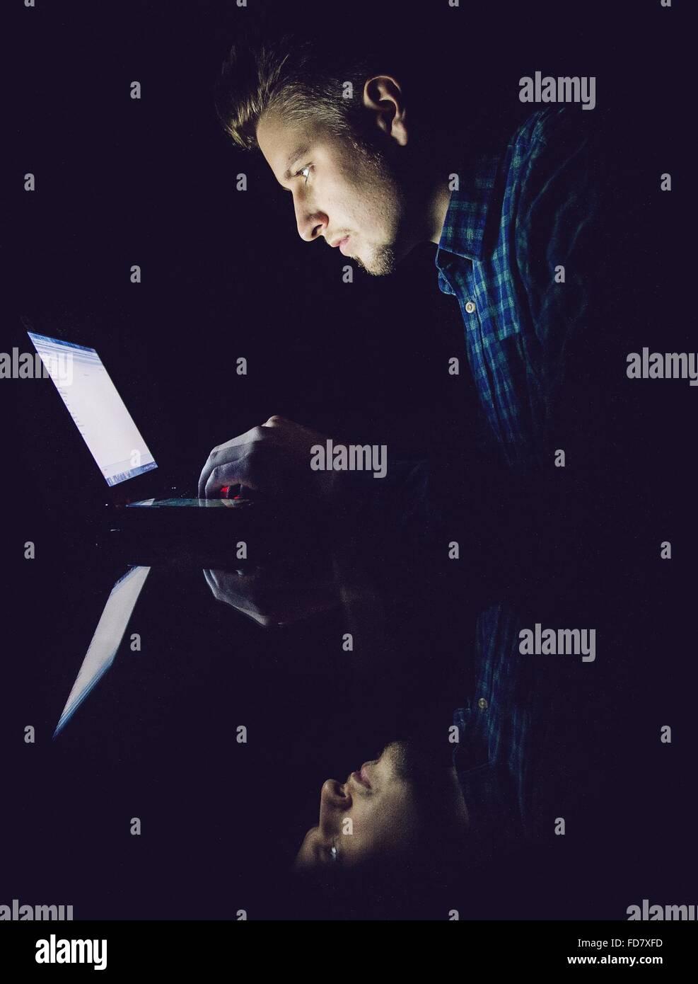 La reflexión del joven en el cristal mientras se utiliza el portátil en el cuarto oscuro Imagen De Stock