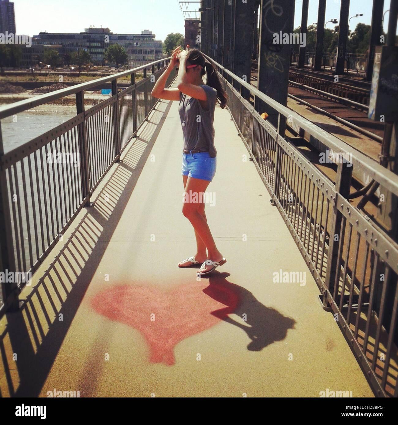 La longitud completa de la Mujer Joven de pie en el puente peatonal con pintura con forma de corazón Imagen De Stock