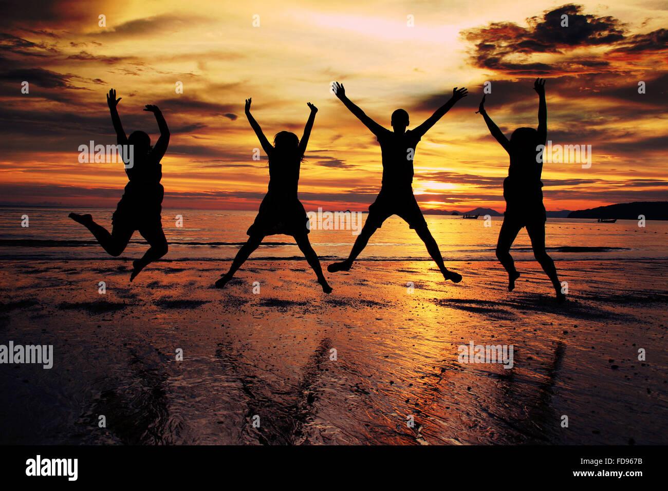 Silueta amigos saltando en la playa durante la puesta de sol Imagen De Stock