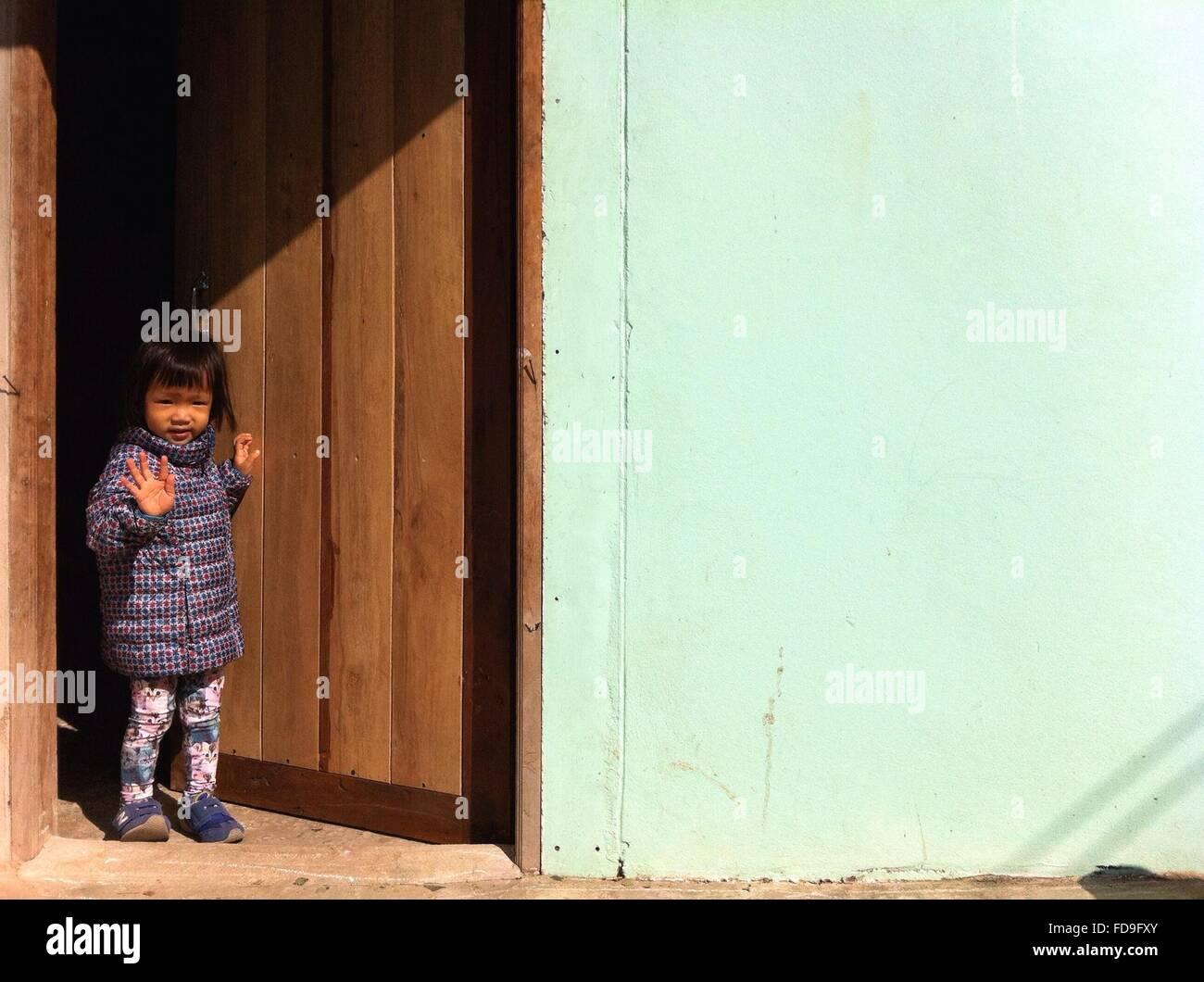 Niña de pie en la puerta y agitando la mano Imagen De Stock