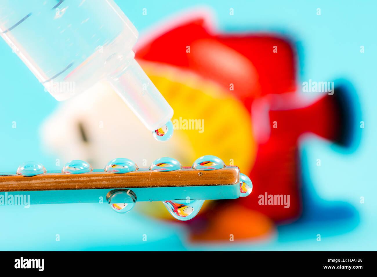 Reflejos en un pez cae desde una jeringa - podría utilizarse para ilustrar la ingeniería genética, Imagen De Stock