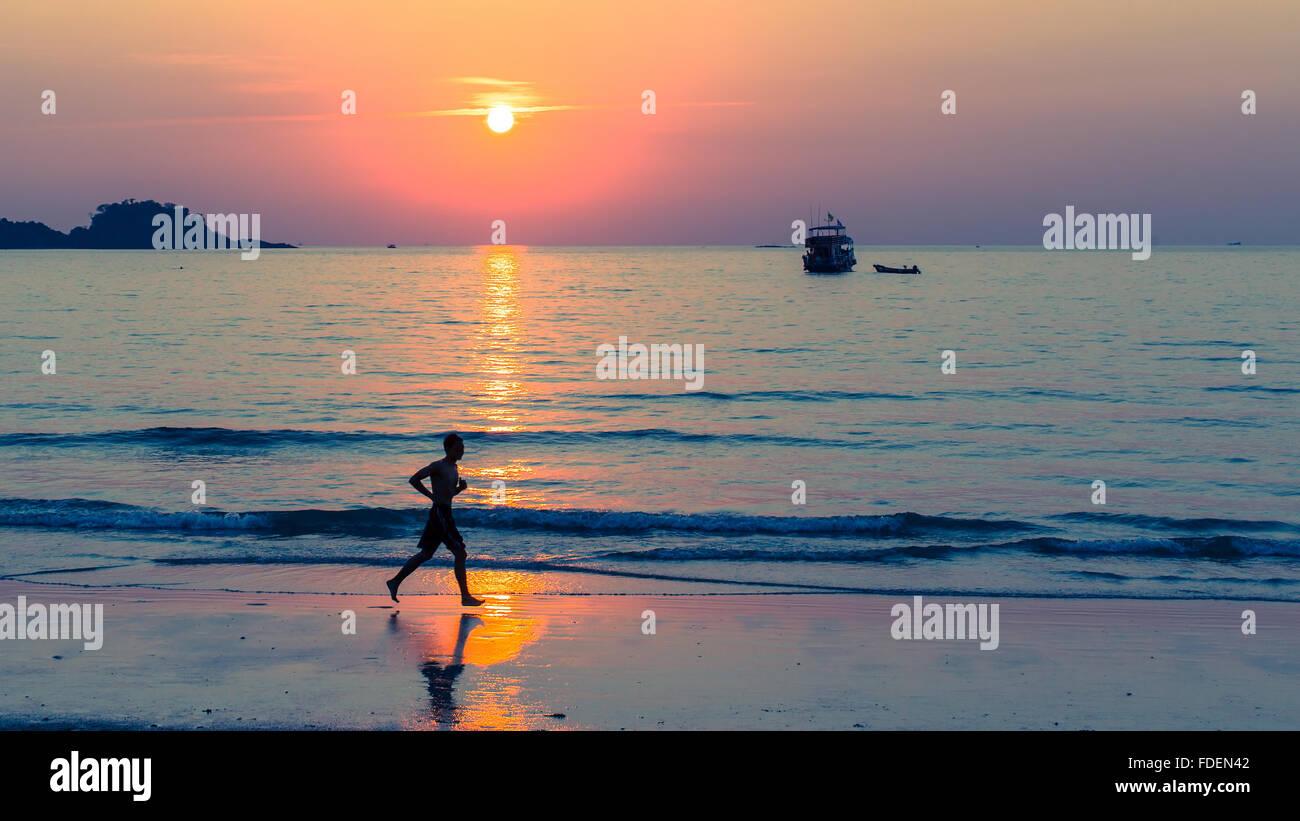 Silueta de hombres corriendo sobre la línea de costa durante la increíble puesta de sol. Imagen De Stock