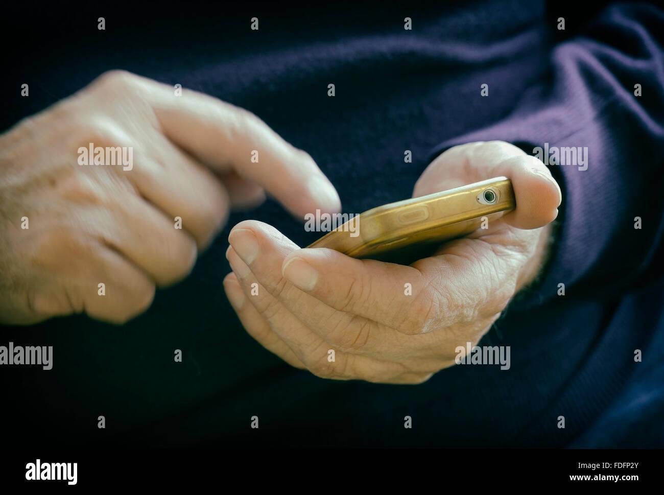 Manos macho introduciendo información en el teléfono inteligente. Imagen De Stock