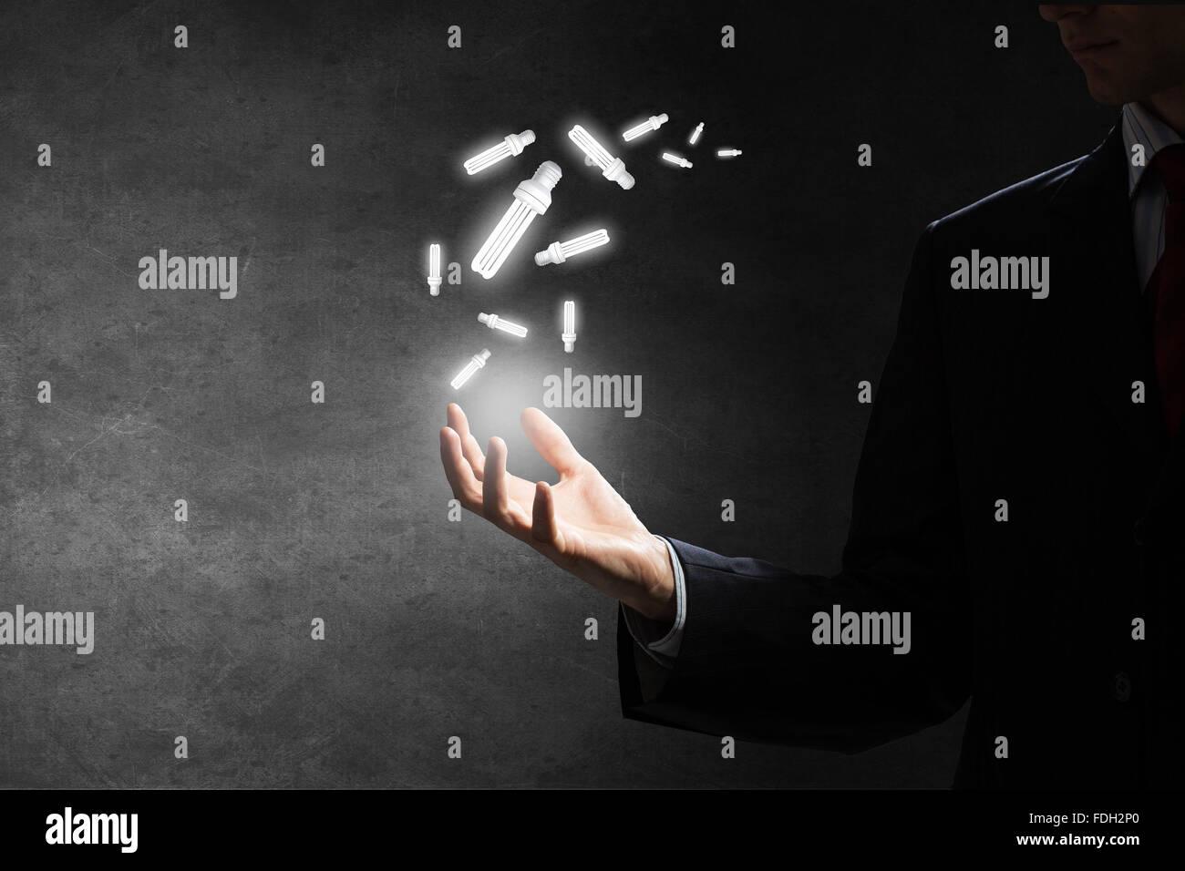 Empresario con bombilla de cristal iluminado en la mano Imagen De Stock
