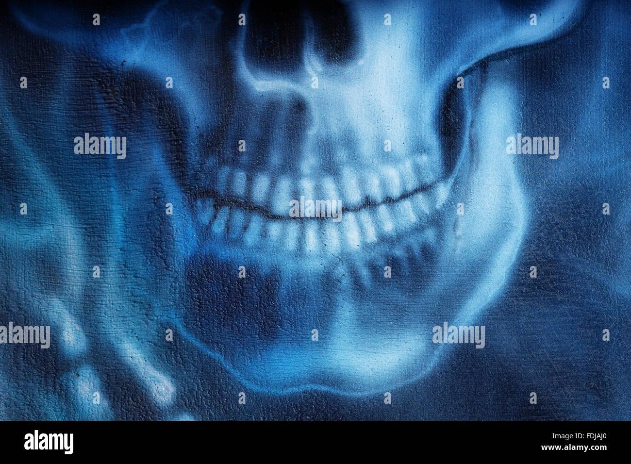 Cráneo y un esqueleto detallada mano y fuego azul sobre fondo negro ...