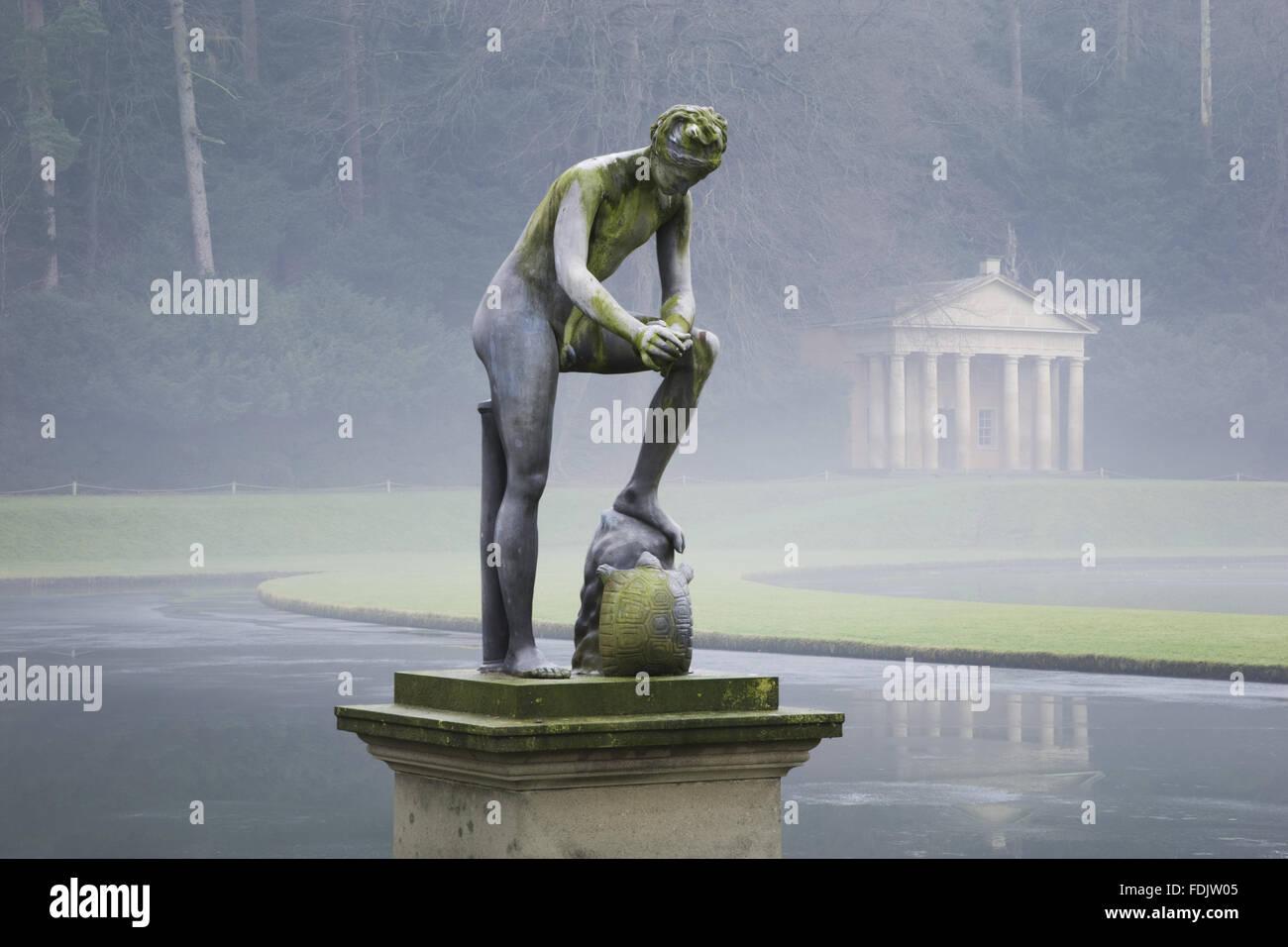 Un invierno brumoso, vista de una estatua delante del templo de la Piedad en Studley Royal Jardín Acuático, North Yorkshire. Los jardines fueron creados en 1716 por John Aislabie y continuada por su hijo William en el decimoctavo siglo posterior. La estatua es de Cincinnat Foto de stock