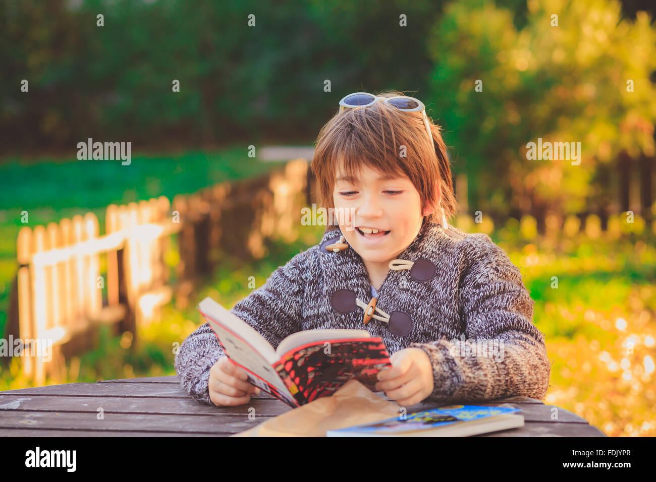 Chico leyendo en el jardín del libro Foto de stock