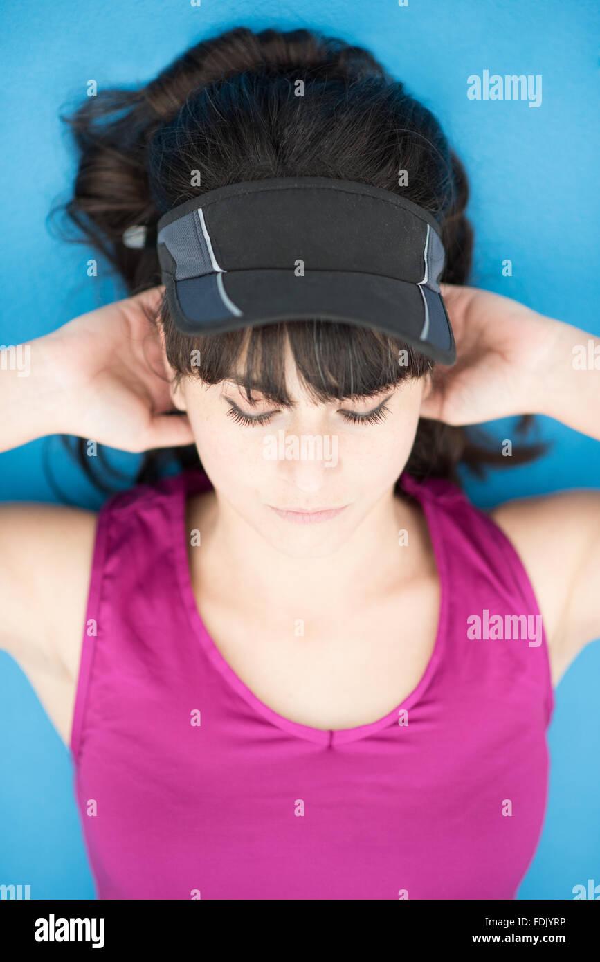Joven mujer acostada el ejercicio con las manos detrás de la cabeza Imagen De Stock