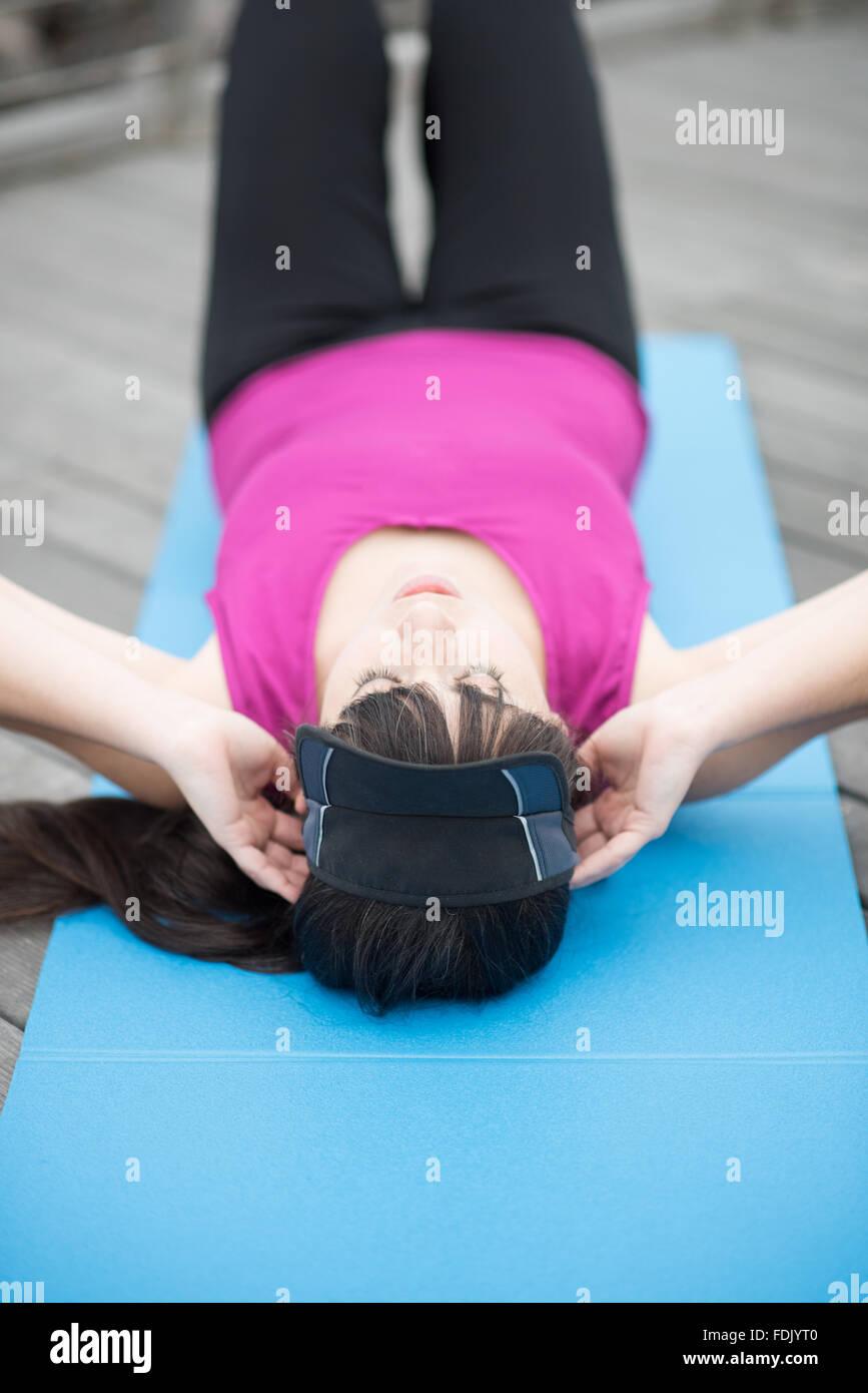 Mujer joven acostado haciendo Sit-ups Imagen De Stock