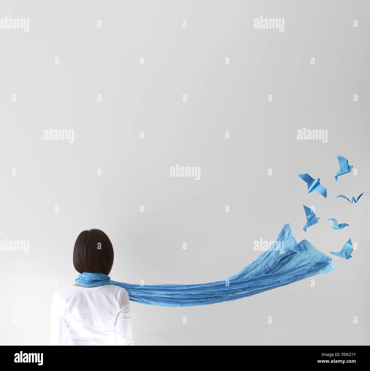 Vista trasera de una mujer con bufanda azul y pájaros de origami Foto de stock